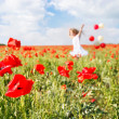 happy girl with colorful balloons running in poppy field — Stock Photo