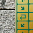 Information board with directional arrows over stone wall - Stock Photo