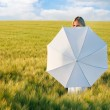 Young beautiful girl behind white umbrella in green field — Stock Photo #12615800