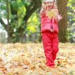 Young happy girl playing in autumn park — Stock Photo