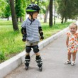 Cute girl looking young boy rollerskating — Stock Photo #12615848
