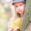 Beautiful young girl with autumn leaves in hands — Stock Photo