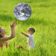 Mother and son playing with earth-like ball — Stock Photo
