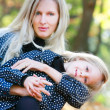 Mother and daughter in autumn park — Stock Photo