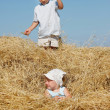 Stock Photo: Two kids playing in haystack