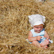 Stock Photo: Cute toddler girl playing in haystack
