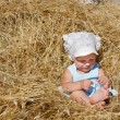 Cute toddler girl playing in haystack — Stock Photo