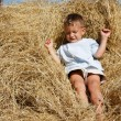 Cute boy playing in hay — Stock Photo