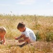 Two kids playing on country road — Stock Photo #12616371
