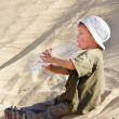 Young boy drinking water in sand desert — Stock Photo