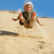 Stock Photo: Young boy jumping in sands