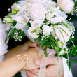 Close up of bride's and groom's hands with wedding bouquet — Stock Photo