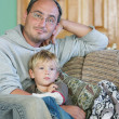 Father and son watch tv at home — Stock Photo #12617716