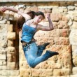 Jumping girl in action over grunge background - Stock Photo