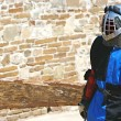 Stock Photo: Knight on stone wall background