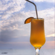 Glass of orange juice on sky background — Stock Photo