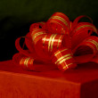 Red ribbon and gift box over black background — Stock Photo