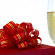 Red gift box and glass of champagne — Stock Photo