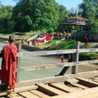 Young monk on wooden bridge - Foto Stock