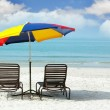 Royalty-Free Stock Photo: Wooden chairs and colorful umbrella on sand beach
