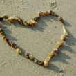 Heart from seashells on sand beach — Stock Photo #12619314