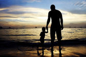 Father and son on sunset sea and sky background — Stock Photo