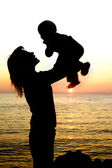 Silhouettes of mother and son partly isolated over white — Stock Photo