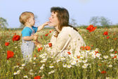 Mother and son playing in flowers — Stock Photo