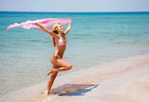 Young happy girl jumping on beach — Stock Photo