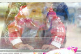 Child looking through glass window in supermarket — Stock Photo