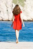 Mladá dívka v červených šatech na moři — Stock fotografie