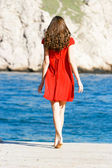 Young girl in red dress on the sea — Stok fotoğraf