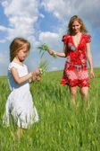 Mother and daughter in green field — Stock Photo