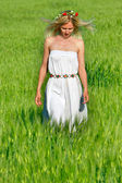 Young girl walking in green field — Stock Photo