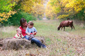Happy mother with two children in autumn park — Stock Photo
