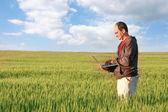 Uomo con il portatile in campo verde — Foto Stock