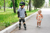 Cute girl looking young boy rollerskating — Stock Photo