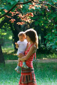 Pregnant woman with baby in park — Stock Photo