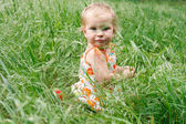 Cute toddler girl in green grass — Stock Photo