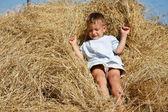 Lindo niño jugando en heno — Foto de Stock