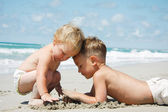 Two kids playing in sand on beach — Stock Photo