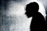 Person's silhouette behind textured glass wall — Stock Photo