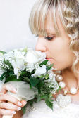 Close up portrait of young bride with wedding bouquet — Stock Photo