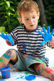 Young boy with his hands in blue paint outdoors — Stock Photo