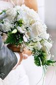 Gros plan des mains du marié et la mariée avec bouquet de mariée — Photo