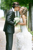 Kissing couple on their wedding day — Stock Photo