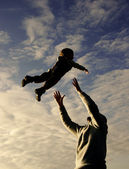 Silhouettes of father and son playing on sky background — Stock Photo