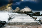 Rocks at stormy sea background — Stock Photo