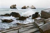 Rocks on stormy sea background — Stock Photo