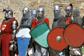Several knights on stone wall background — Stock Photo